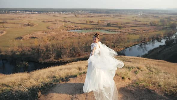 Thumbnail for Beautiful Millennial Bride Stands on a Hill Among the Grass and Waves Her Gorgeous Veil Wedding