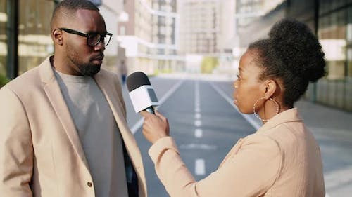 Afro-American Businessman Giving Interview to Female Journalist