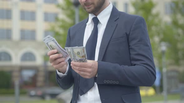 Unrecognizable Rich Man Counting Money and Smiling. Wealthy Caucasian Young Businessman Standing
