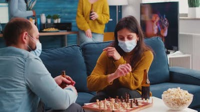 Friends Having Fun Playing Chess in Living Room During Global Pandemic