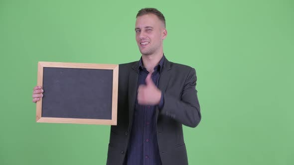 Thumbnail for Happy Handsome Businessman in Suit Holding Blackboard Giving Thumbs Up
