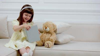 Girl with Teddy Bear Reading a Book