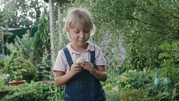Thumbnail for Girl Eating Sour Apple in Green Garden