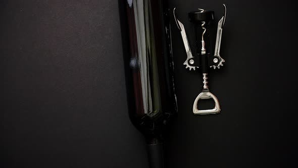 Thumbnail for Red Wine Bottle and Corkscrew on Black Matte Background.