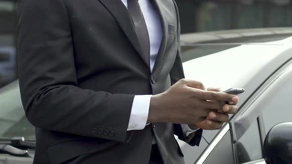Cover Image for African American Man in Business Suit Typing Message Standing Near His Car