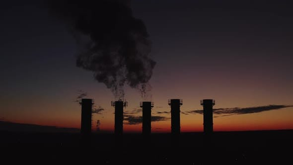 Thumbnail for Silhouettes of Five Cooling Towers Against the Backdrop of a Big City and Sunset. Beautiful Sunset