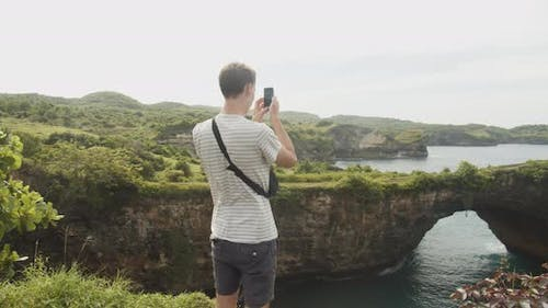Medium Close Up Shot of a Male Tourist Taking Pictures of the Broken Beach Pasih Uug in Bali with