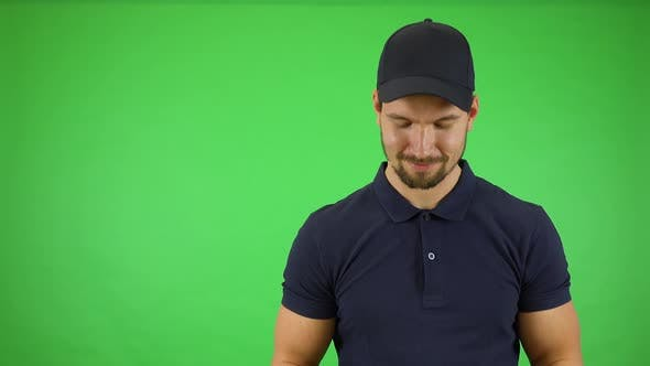 Thumbnail for A Young Handsome Mailman Offers a Package To the Camera with a Smile - Green Screen Studio