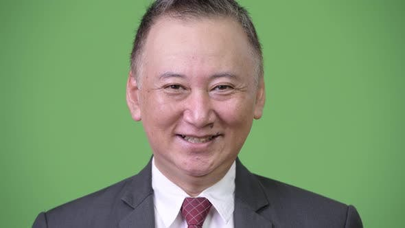 Thumbnail for Mature Happy Japanese Businessman Smiling Against Green Background