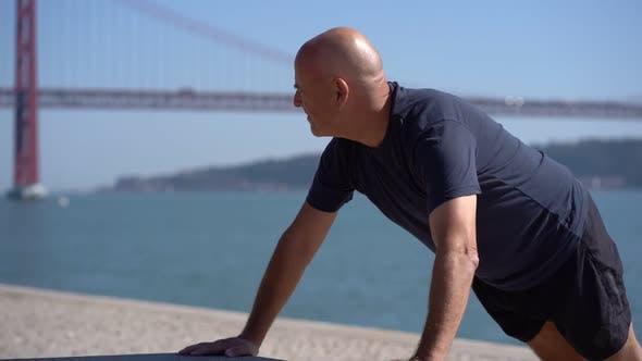 Cover Image for Bald Mature Sportsman Doing Push Ups at Riverside