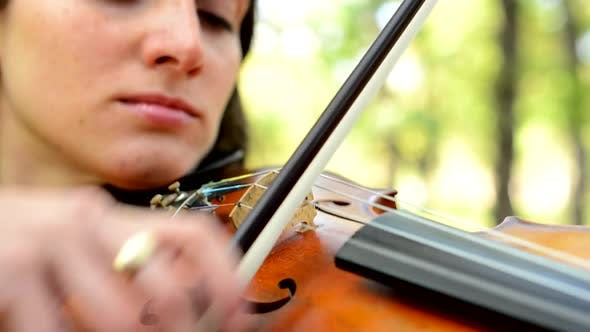 Thumbnail for Young Attractive Happy Woman Play on the Violin in the Park - Concentrate on the Play