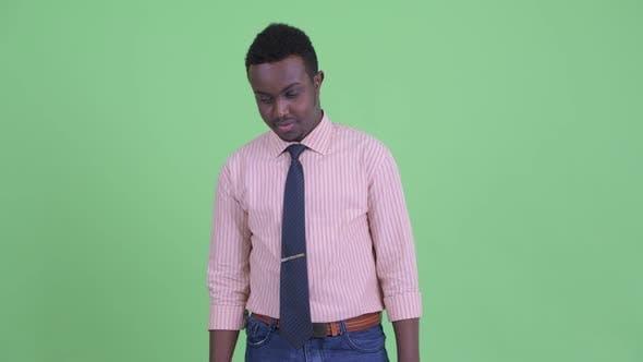 Thumbnail for Ernst junge afrikanische Geschäftsmann denken und schauen nach unten