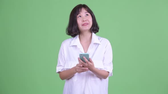 Thumbnail for Happy Beautiful Asian Businesswoman Thinking While Using Phone