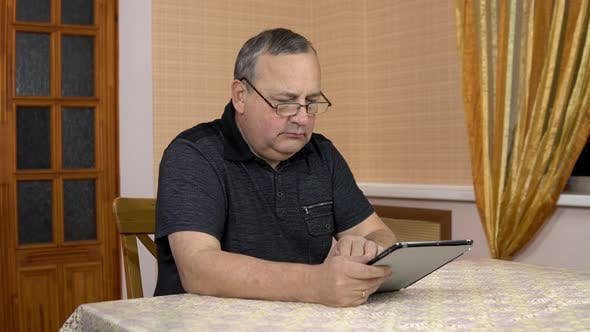 Thumbnail for Serious Man Uses a Tablet, Old Man Works with a Tablet While Sitting at the Table