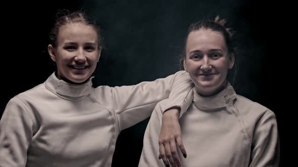 Thumbnail for Two Young Smiling Women Fencers Standing in the Studio and Looking in the Camera