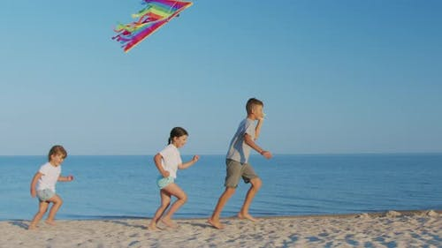 A Happy Children Play Kite Together on the Beach. Summer Holidays.