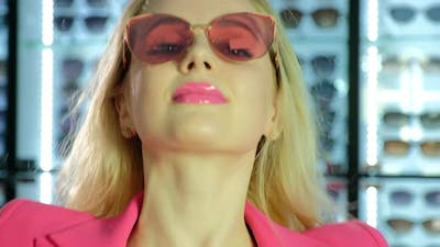 Woman in Pink Suit with Sunglasses Shakes Hair in Store