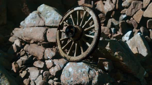 Old Wooden Wheel on Rocks