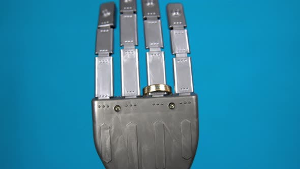 Thumbnail for A Mechanical Hand with a Ring on the Ring Finger. Gray Cyborg Hand on a Blue Background. The Camera