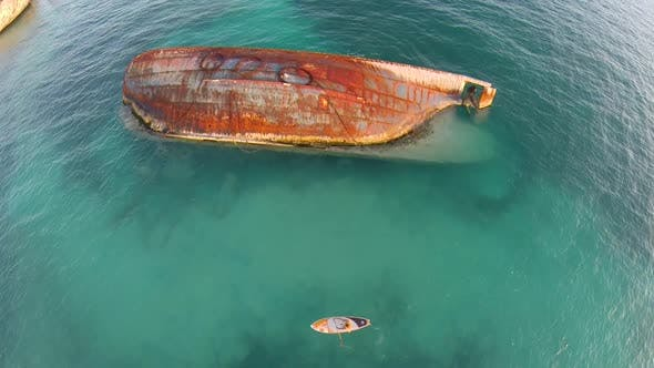 Aerial shot of young woman sup standup paddleboarding near a shipwreck in the Caribbean.
