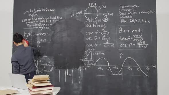 Woman Wiping Blackboard with Rag