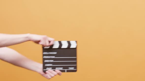 Female Hands Using a Clapperboard Over a Yellow Background