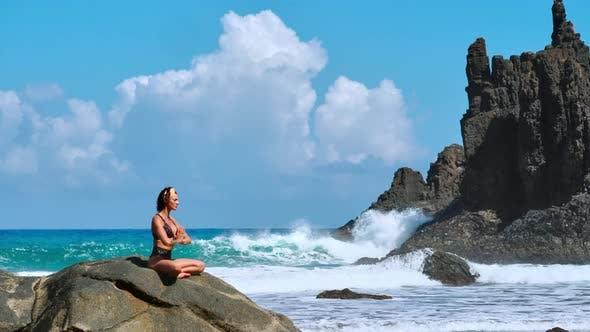Cover Image for Serene Meditation Yoga. Brunette Tourist Woman Meditating in Lotus Position on Promontory Above