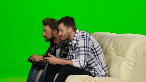 Two Guys Playing Video Games with Wireless Control Pad. Green Screen