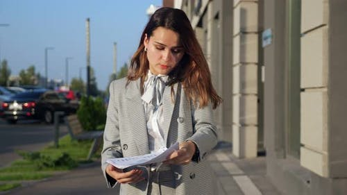 Young Woman in a Business Suit is Emotionally Talking on the Phone and Looking at the Documents