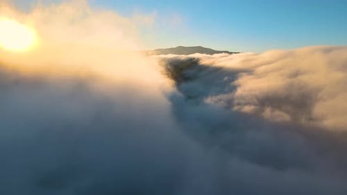 Aerial view of landscape above foggy fast moving clouds covering mountain hills at sunset.