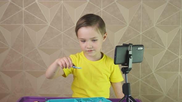 Junge sitzt zu Hause an einem Tisch vor dem Telefon und kommuniziert per Video anruf mit Freunden