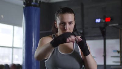Female Fighter Punching the Air and Posing for Camera in Gym