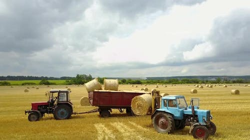 Semi Truck Loading Straw Bales. Semi truck and tractor loaded straw bales in countryside