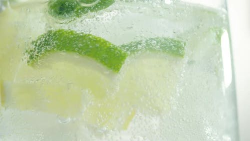 Bubbles Rise Up Inside Glass of Sparkling Water with Lime