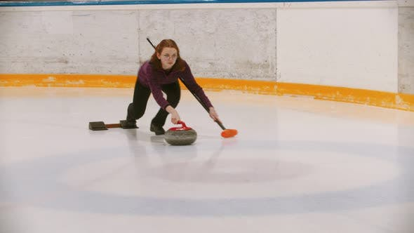 Thumbnail for Curling - a Woman in Glasses Pushes Off on the Ice Field with a Granite Stone Holding a Brush