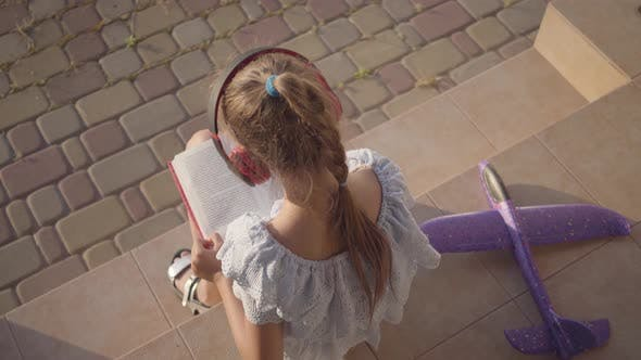 Thumbnail for Pretty Cute Little Girl in Headphones Reading the Book, the Small Plane Lying on the Porch