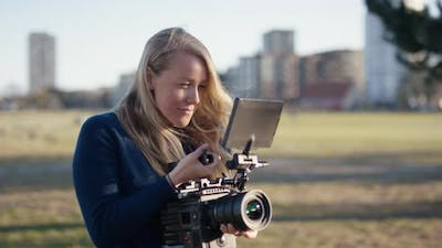 Female Film Maker Watching Monitor And Filming