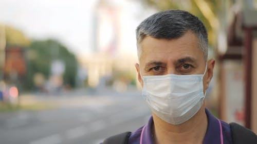 Portrait of a Man in a Medical Mask Waiting for a Bus at a Bus Stop