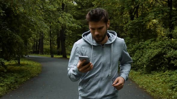 Thumbnail for Young Powerfull Runner Outside in Autumn Nature Park with Phone