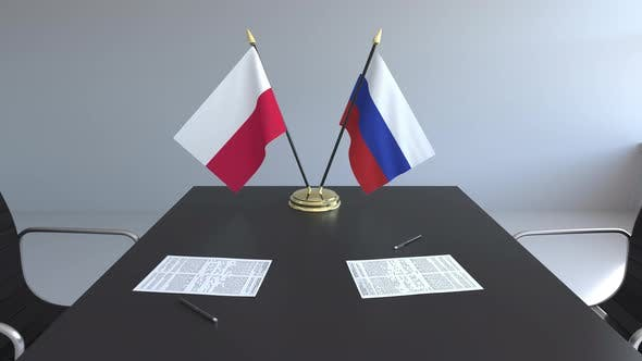 Flags of Poland and Russia and Papers on the Table