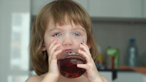 Little Girl Drinks Cherry Juice From Glass Looks at Camera Laughs and Smiles