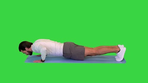 Young Caucasian Male in Sportswear Doing Push Ups on a Green Screen Chroma Key