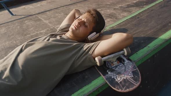Skater in Headphones Relaxing in Skatepark