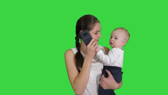 Thumbnail for Motherhood, Multi-tasking, Family and People Concept - Happy Mother with Baby Calling on Smartphone