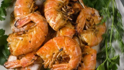 Delicious Red Shrimps with Dill and Parsley on White Plate