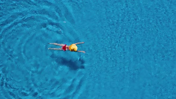 Thumbnail for View From the Top As a Woman in a Red Swimsuit and a Big Yellow Hat Swims in the Pool
