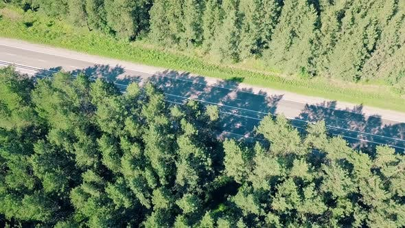 Thumbnail for Aerial: Flying Over the Highway, Which Passes Cars and Trucks in the Forest. Direction To the Auto