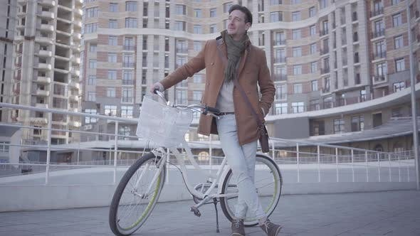 Cover Image for Handsome Serious Man in Brown Coat and Light Blue Jeans Standing with His Bicycle in the City in