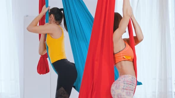 Thumbnail for Two Women Having an Aero Yoga Training in the Studio - Hanging in the Hammocks