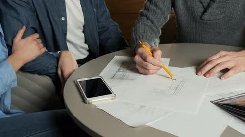 Young Couple at a Meeting with an Interior Designer. Placement of Kitchen Furniture. Architect Draws